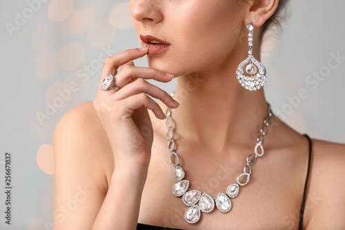 Young woman with beautiful jewelry on light background, closeup Tapéta, Fotótapéta