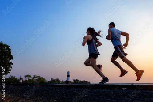 Fototapeta Running at sunrise couple exercising for marathon and workout