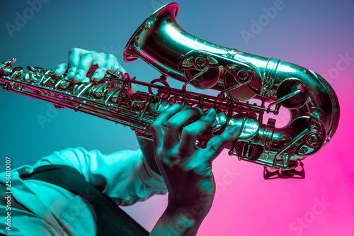 Canvas Print African American handsome jazz musician playing the saxophone in the studio on a neon background