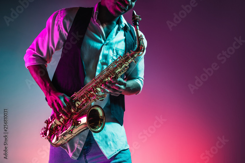 Photo African American handsome jazz musician playing the saxophone in the studio on a neon background