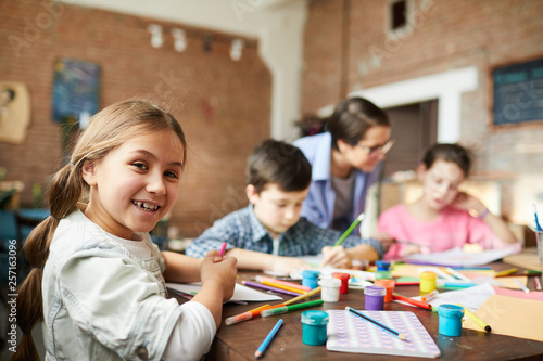 Leinwand Poster Portrait of cute little girl looking at camera while enjoying art class with gro