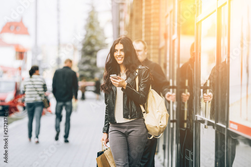 Foto Young pretty latin woman walking near shops in city centre