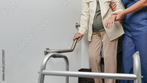 Photo Elderly woman holding on handrail with caregiver