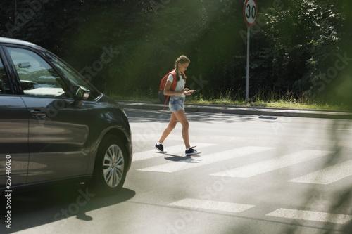 Foto Girl using smartphone while walking through crosswalk next to a car