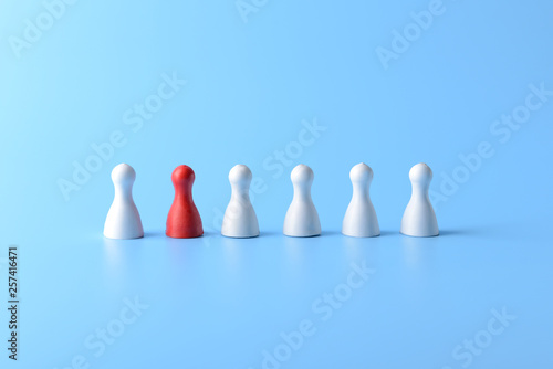 Fotografiet Red pawn among white ones on color background