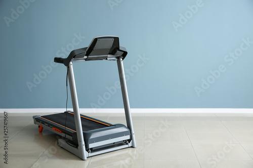 Fotografia Modern treadmill near color wall in gym