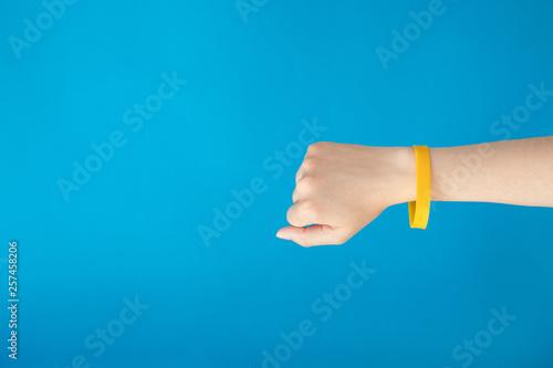 Fotografia Female hand with empty yellow bracelet on blue background