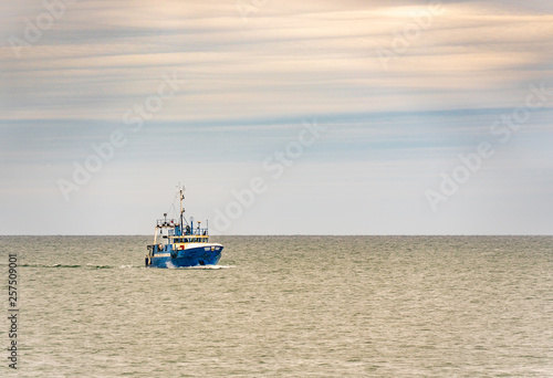 Small single fishing boat at the open sea with scenic sky. Fototapet