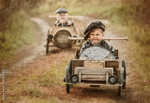 Fototapeta Competition between the two boys on improvised racing cars