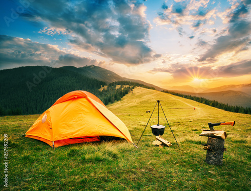 Fotografia Tourist camp in mountains with tent and cauldron over fire at sunset
