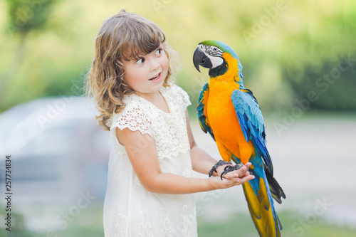 Making photo of exotic animals. Little girl with macaw parrot Fototapeta