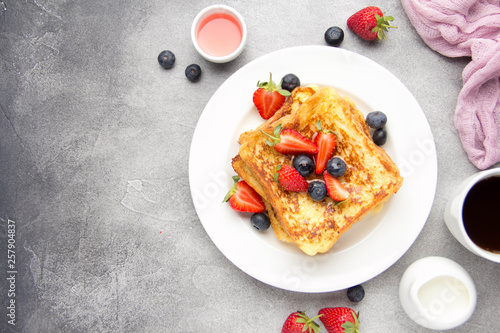 Платно French toast with berries (blueberries, strawberries) and sauce, traditional sweet dessert of bread with egg and milk
