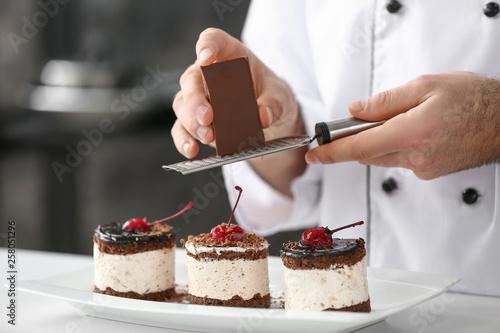 Fotografie, Obraz Male confectioner decorating tasty dessert in kitchen, closeup