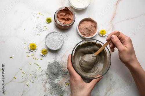 Stampa su Tela Woman preparing cosmetic clay on light background