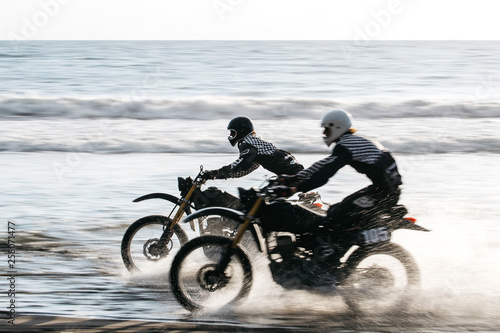 Valokuva Two friends racing on custom retro style cafe racer black motorcycles on the bea