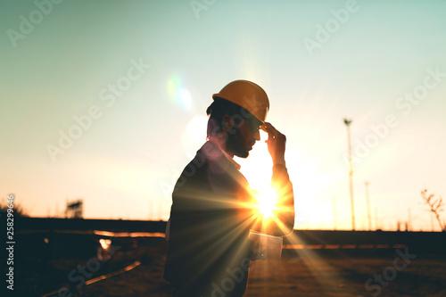 Fototapeta Sagoma di un operaio che indossa il caschetto protettivo in testa per la sua sicurezza prima di entrare in cantiere