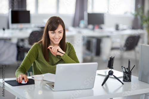 Foto Beautiful smiling Caucasian businesswoman sitting in modern office and using laptop