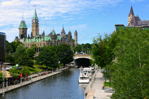 Looking down a boat lined Rideau Canal towards Parliament Hill, Ottawa, Ontario, Canada