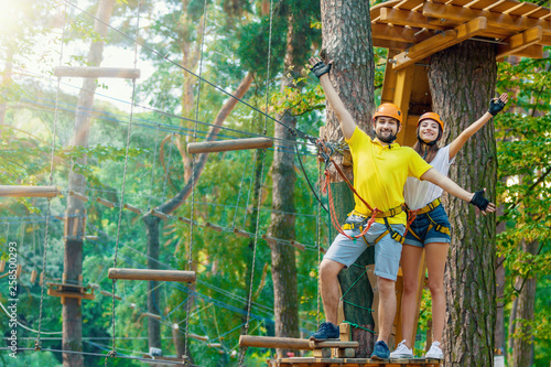 Tableau sur Toile Young woman and man in protective gear are standing on wooden board on high tree, posing and smiling