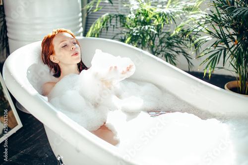 Slika na platnu Playful young caucasian woman enjoying foam bath at home