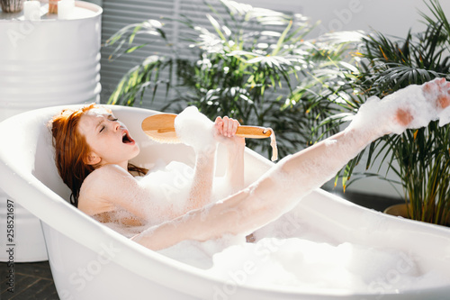 Vivacious emotional young woman with red hair bun taking bath at home, being in Fototapeta