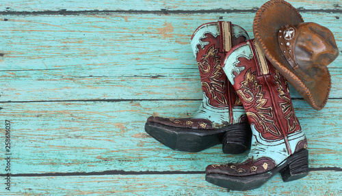 Tela cowboy boots and hat laying on a teal background