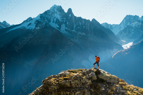 Fotografía A hiker on top of a rocky summit in the mountains of the Alps