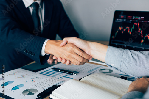 Two businessmen agreed to buy and sell shares by shaking hands in order to accept mutual investment Fototapeta