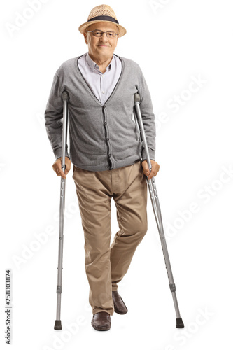 Leinwand Poster Senior man walking with crutches and smiling at the camera