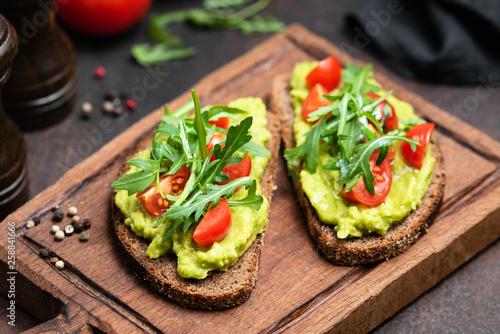 фотография Vegan or Vegetarian Toast with mashed avocado, arugula served on wooden board