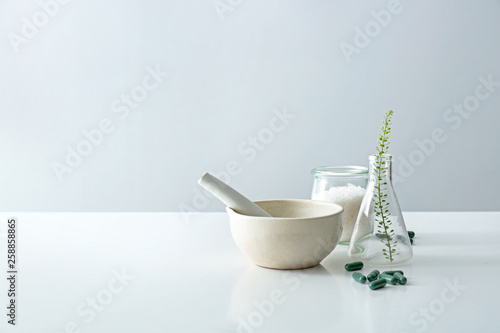 Fotografia Composition with mortar, flask and plant based pills on table