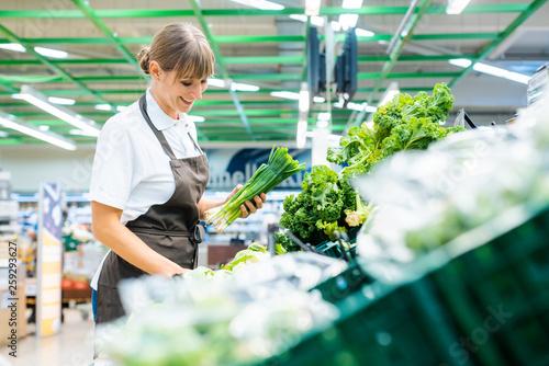 Carta da parati Shop assistant in supermarket re-stocking fresh vegetables