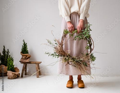 Frau hält Kranz für Weihnachten in der Hand