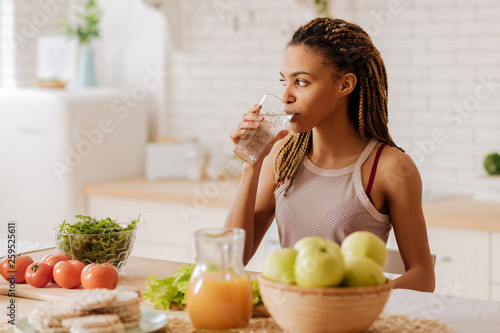 Valokuva Slim and fit woman drinking water before having breakfast