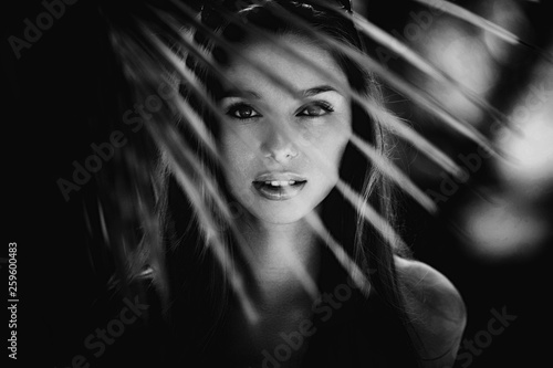 Black and white fashion portrait of beautiful young blonde girl standing in palms and watching with her perfect eyes on Bali