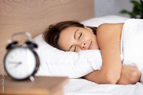 Stampa su Tela Pretty female sleeping on bed alarm clock on bedside table