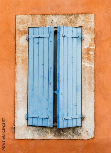 Fototapeta premium stara niebieska drewniana okiennica na pomarańczowej ścianie - Roussillon, Prowansja, Francja