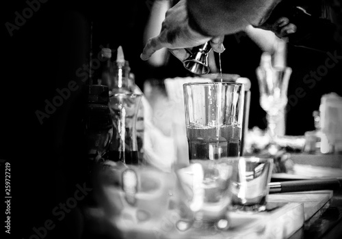 Tableau sur Toile Bartender making alcohol cocktail at bar counter at nightclub, barman is making