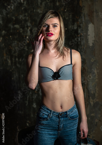 Fotografiet Beautiful young girl in bodice and jeans in the old studio