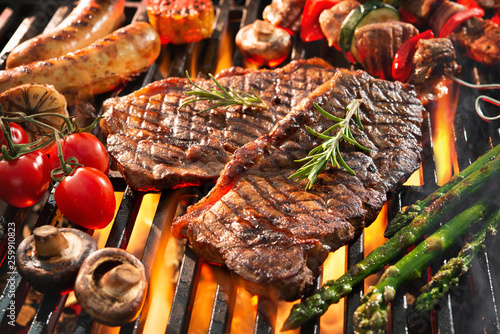 Foto Delicious grilled meat with vegetables sizzling over the coals on barbecue