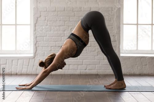 Fotografija Woman practicing yoga, Downward facing dog, adho mukha svanasana