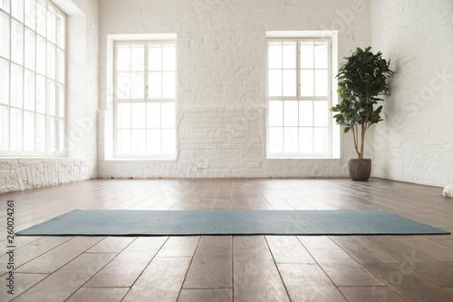 Fotomural Unrolled yoga mat on wooden floor in yoga studio