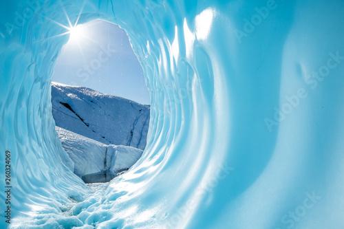 Fotografia, Obraz Sun shining into the entrance of a large round ice cave in the Matanuska Glacier in Alaska