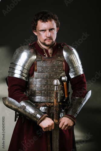 Fotografie, Tablou Medieval man knight in armor and weapon on dark background