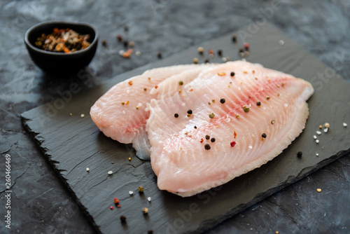 Fresh tilapia fillet ready to be cooked, black wooden background. Side view, copy space