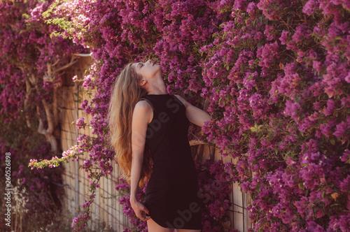 Stampa su Tela Portrait of girl among purple bougainvillaea