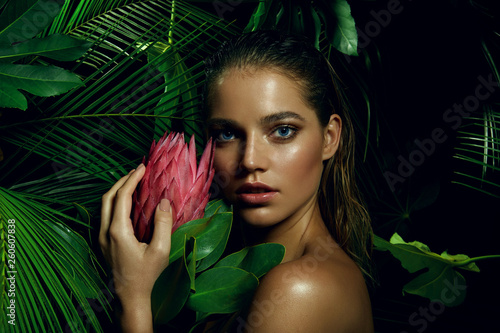 A beautiful tanned girl with natural make-up and wet hair stands in the jungle among exotic plants.