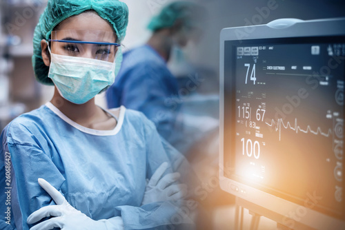 Team of doctors or surgeons with electrocardiogram monitor in hospital surgery operating emergency room showing patient heart rate, during coronavirus or covid-19 crisis, medical concept Fototapeta