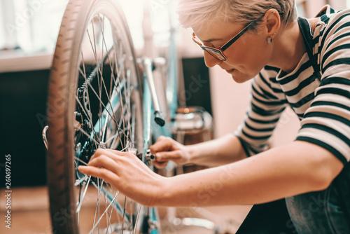 Beautiful Caucasian female worker with short blonde hair and eyeglasses crouching and repairing bicycle. Bike workshop interior.