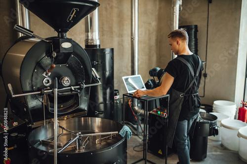 Fotografija Young man coffee roaster working in roastery, coffee roasting in specialty coffee roastery